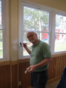 Father Peter Casparian painting the window trim